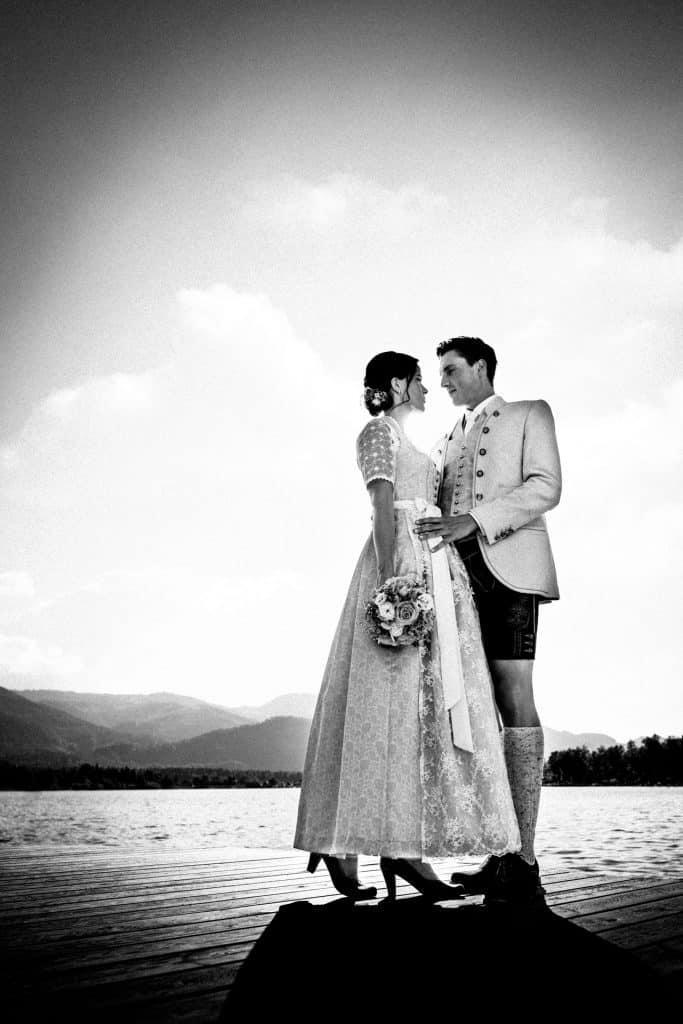 Hochzeitspaar steht auf einem Steg am Wolfgangsee