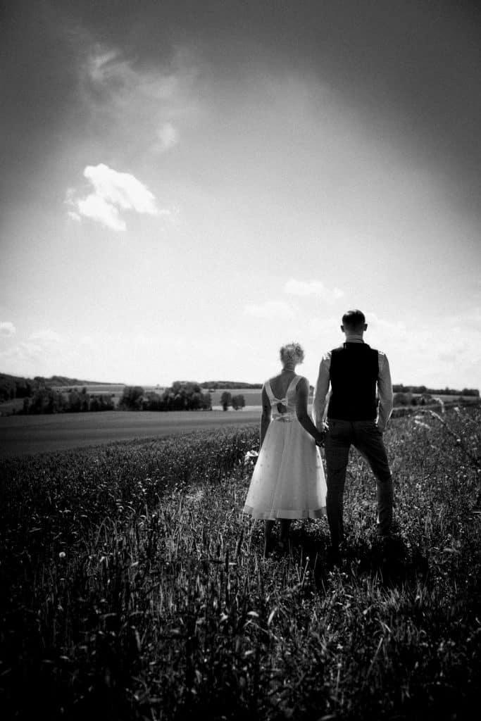 Brautpaar steht auf einem Feld und blickt in die Ferne