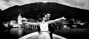 Brautpaar steht in einem Boot am Wolfgangsee und jubelt