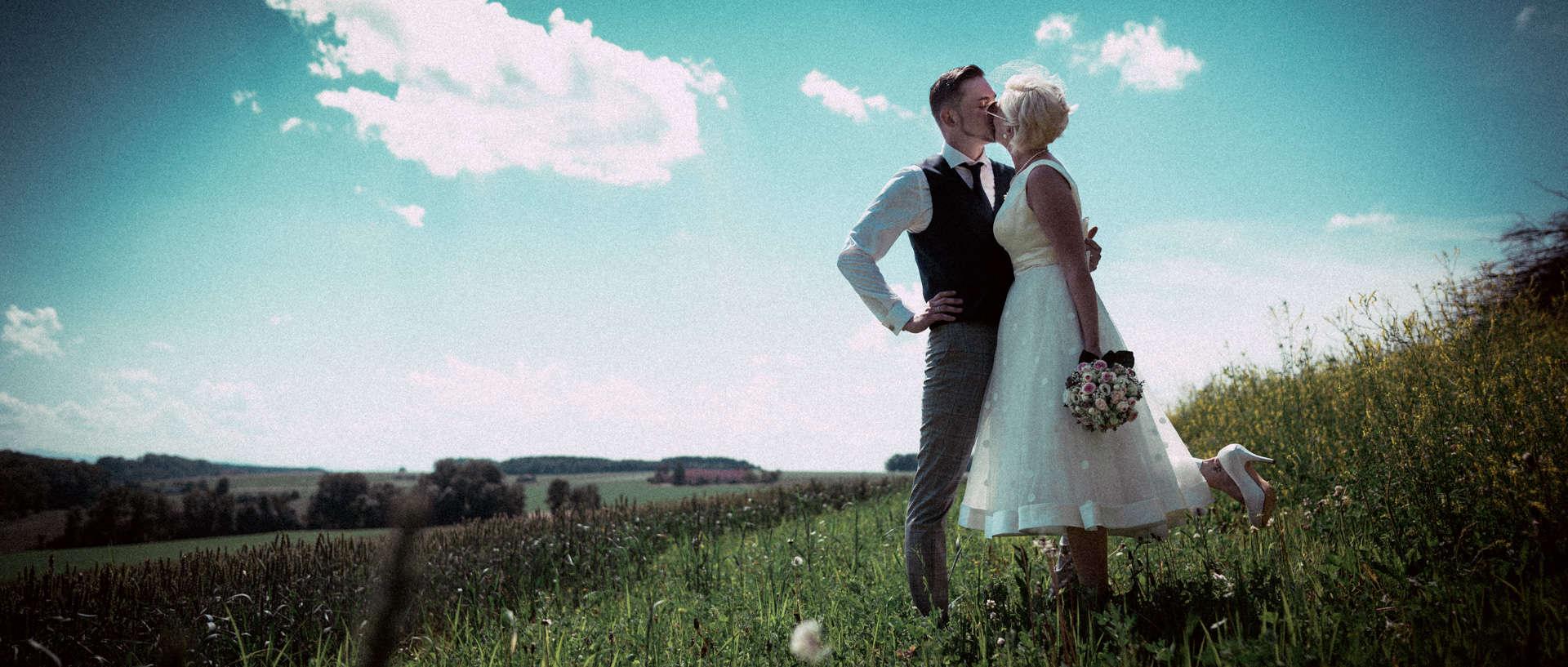 Hochzeitspaar küsst sich auf einer Wiese vor blauem Himmel