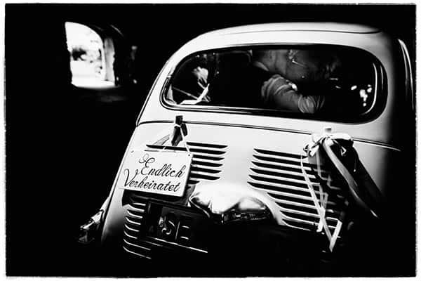 Ein Brautpaar küsst sich in einem Fiat Kleinwagen. Am Heck ist ein Schild mit Endlich Verheiratet angebracht.
