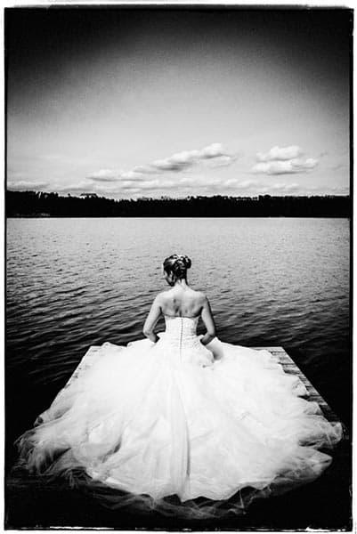 Eine Braut mit weitem Hochzeitskleid sitzt an einem Steg an einem See