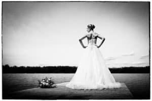 Braut steht auf einem Steg am See.