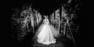 Hochzeits Shooting mit einer Braut. Diese steht auf einer Brücke und lächelt mir zu.