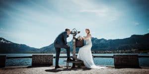 Hochzeitspaar steht an einem Fernglas am Mondsee