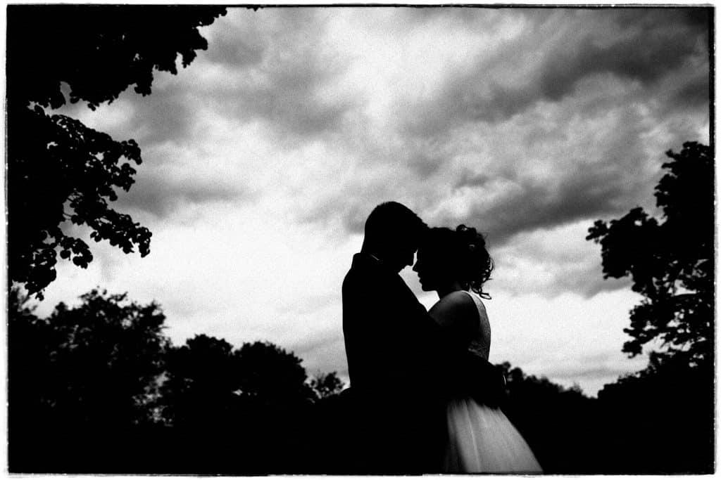 Hochzeitspaar steht vor bewölktem Himmel